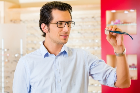 optician: Young man at optician with glasses, he might be customer or salesperson