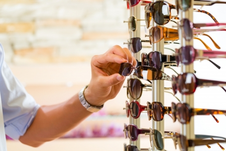 spec: Young man (only hands) at optician with glasses, he might be customer or salesperson and is looking for sunglasses