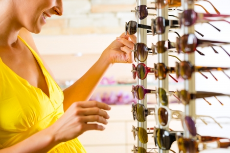 specialized: Young woman at optician with glasses, she is customer to the shop and buying some sunglasses Stock Photo