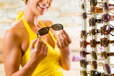 Young woman at optician with glasses, she is customer to the shop and buying some sunglasses photo