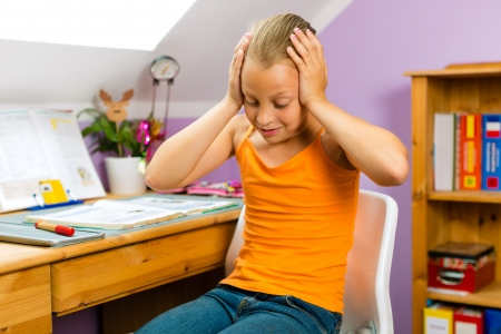 Family - child sitting at home at her desk and doing homework and she does not have much fun photo