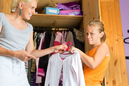 Family - child and mother in front of closet or wardrobe, teenager should put on a dress but does not like it photo
