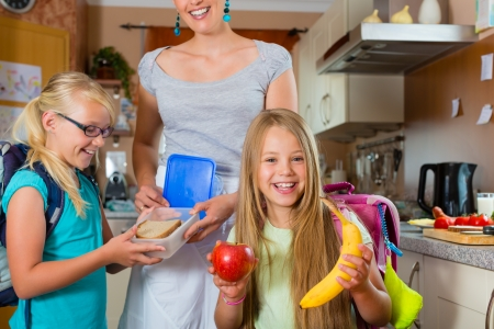 niños desayunando: Familia - madre preparando el desayuno para sus hijos en la mañana y una merienda para la escuela