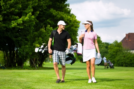 golf cap: Young sportive couple playing golf on a golf course, they walking to the next hole