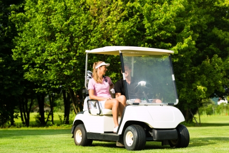 Young sportive couple playing golf on a golf course, they driving with golf cart photo