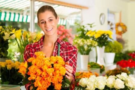 flower shop: Female florist in flower shop or nursery presenting roses