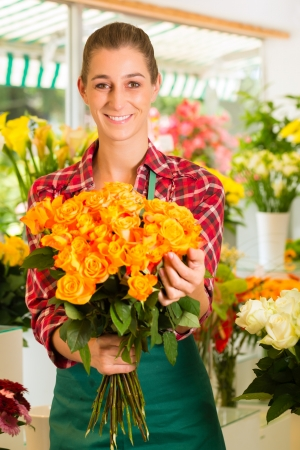 Female florist in flower shop or nursery presenting roses photo