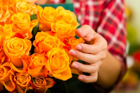 florist shop: Female florist in flower shop or nursery presenting roses, close-up
