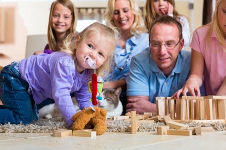 familia jugando: Familia que juega con bloques de juguete y un gato en casa en el suelo