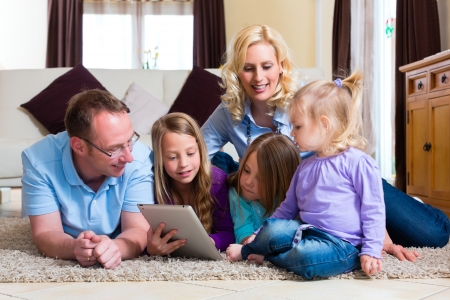 computer game: Family - mother, father, daughters - playing with tablet computer lying on the floor at home Stock Photo