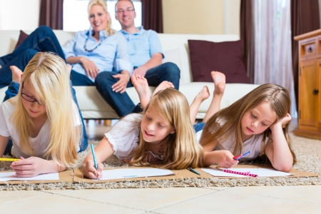 Family, mother, father and daughters are at home, the children coloring on the floor photo