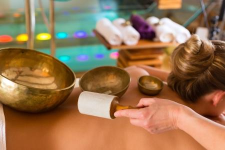Vrouw in wellness-en spa-instelling met een klankschaal massage therapie