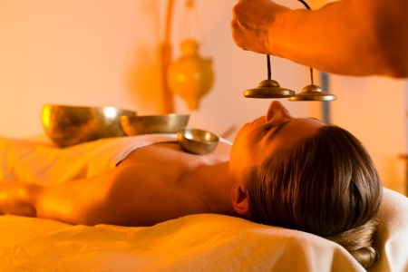 Woman in wellness and spa setting having a singing bowl massage therapy, the therapist is waking her up with cymbals photo