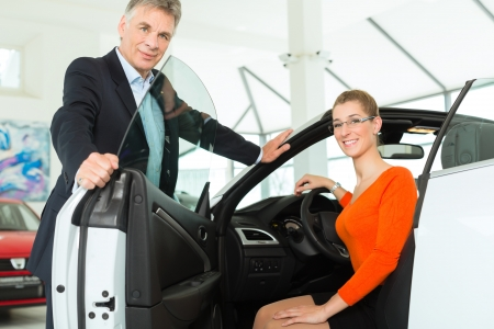 Young woman with mature man sits in car on driver seat with her hand on the steering wheel in a car dealership, obviously she is buying or selling the convertible photo