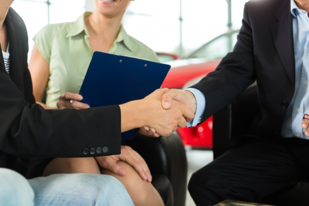Two men in business suits shaking hands after a successful car purchase in front of a woman holding documents in a light car dealership photo