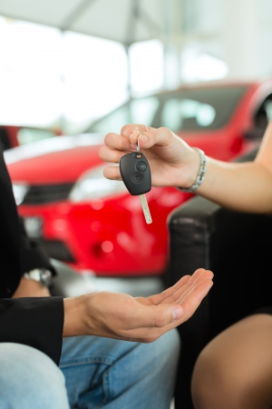 Man at a car dealership buying an auto, the female sales rep giving him the key, macro shot with focus on hands and key Stock Photo - 15678074