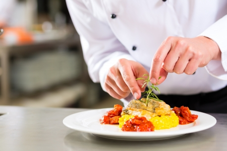 ホテルやレストランの台所の調理でシェフ、彼は皿に料理を仕上げ 写真素材
