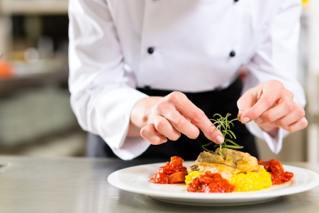 fine fish: Female Chef in hotel or restaurant kitchen cooking, only hands, she is finishing a dish on plate Stock Photo