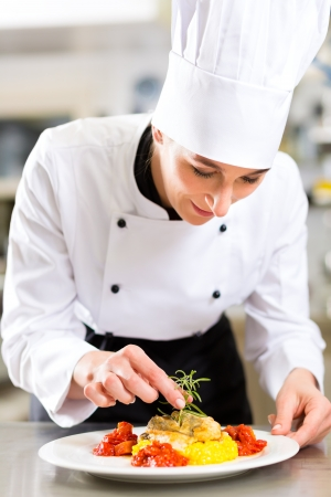 Female Chef in hotel or restaurant kitchen cooking, she is finishing a dish on plate photo
