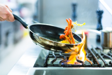 Chef in restaurant kitchen at stove with pan, doing flambe on food photo