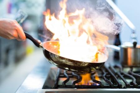 cuisine: Le chef de cuisine du restaurant au po�le avec po�le, faire flamber sur les denr�es alimentaires
