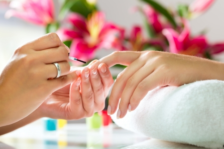 nail salon: Woman in a nail salon receiving a manicure by a beautician Stock Photo