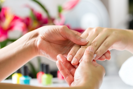 hand massage: Woman in a nail salon receiving a manicure by a beautician, she is getting a hand massage