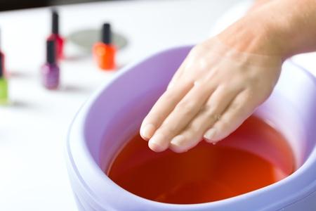 paraffine: Vrouw in een nagelsalon het ontvangen van een manicure, is ze baadt haar handen in paraffine of was Stockfoto