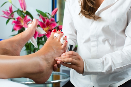 Woman receiving pedicure in a Day Spa, feet nails get polish photo