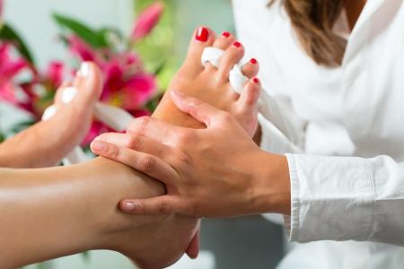 Mujer que recibe pedicure en un Day Spa, uñas pies conseguir pulido y ella está recibiendo un masaje en los pies Foto de archivo
