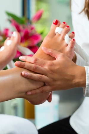 nail scissors: Woman receiving pedicure in a Day Spa, feet nails get polished and she is getting a foot massage