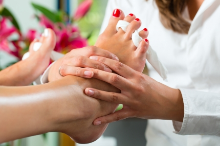pedicure: Woman receiving pedicure in a Day Spa, feet nails get polished and she is getting a foot massage