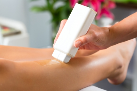 remove: Young woman in Spa getting legs waxed for hair removal