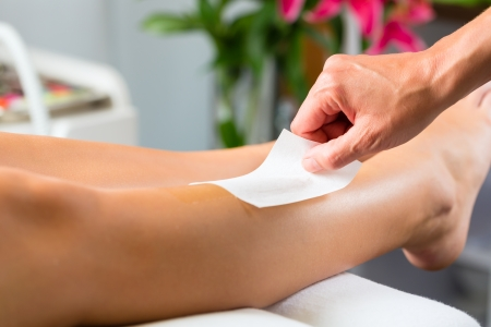 beautician: Young woman in Spa getting legs waxed for hair removal