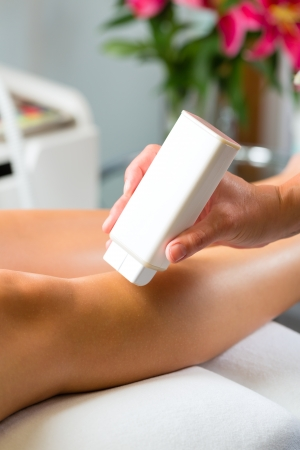 Young woman in Spa getting legs waxed for hair removal photo