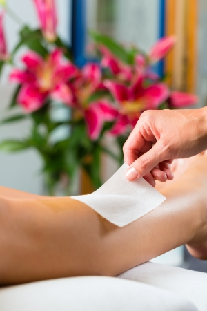 hot legs: Young woman in Spa getting legs waxed for hair removal