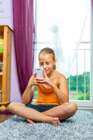 Family - child with cell or smartphone at home in the living room photo