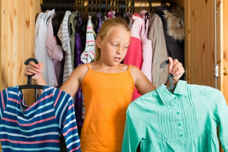 closets: Family - child or teenager in front of her closet or wardrobe and looking for outfit Stock Photo