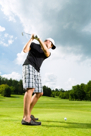 Young golf player on course doing golf swing, he presumably does exercise photo