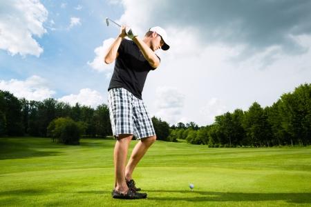 Junge Golfer auf Kurs zu tun Golfschwung, er vermutlich ausübt,