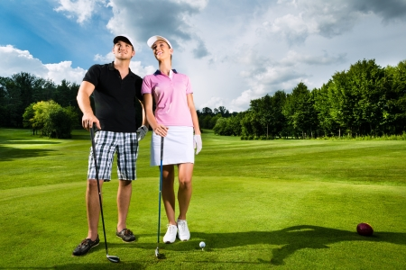 woman golf: Young sportive couple playing golf on a golf course, they certainly do exercise or have training Stock Photo