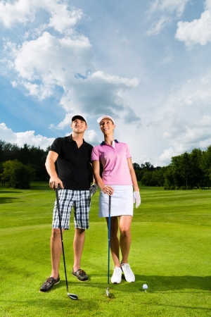 Young sportive couple playing golf on a golf course, they certainly do exercise or have training Stock Photo - 15678230