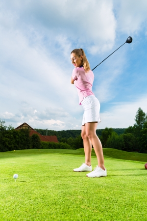Young female golf player on course doing golf swing, she presumably does exercise photo