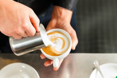 Barista making cappuccino in his coffeeshop or cafe, close-up photo