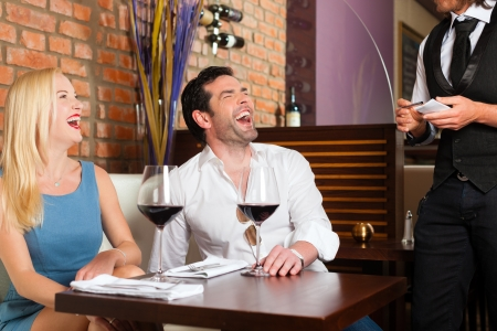 Attractive young couple drinking red wine in restaurant or bar, the waiter is taking the order photo