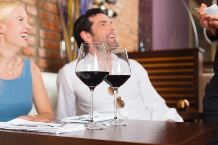 Attractive young couple drinking red wine in restaurant or bar, the waiter is taking the order Stock Photo - 15784970
