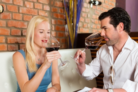 Attractive young couple drinking red wine in restaurant or bar, it might be the first date Stock Photo - 15785009