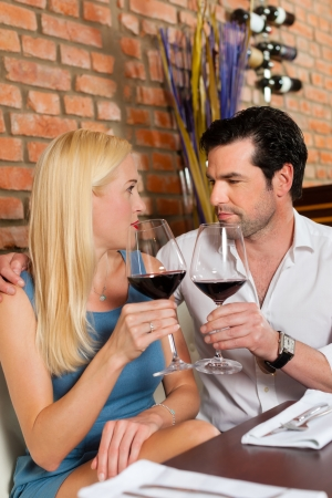 might: Attractive young couple drinking red wine in restaurant or bar, it might be the first date
