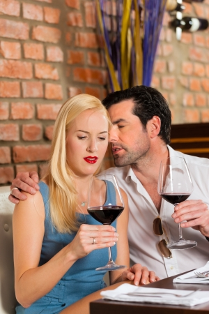 Attractive young couple drinking red wine in restaurant or bar, it might be the first date Stock Photo - 15785051