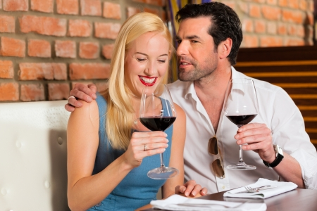 Attractive young couple drinking red wine in restaurant or bar, it might be the first date Stock Photo - 15785041